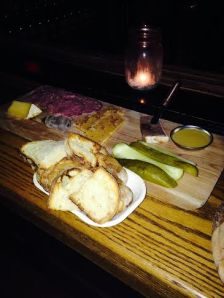 Platter with pickles, mustard, venison terrine, fidge, duck sausage and cloth bound cheddar